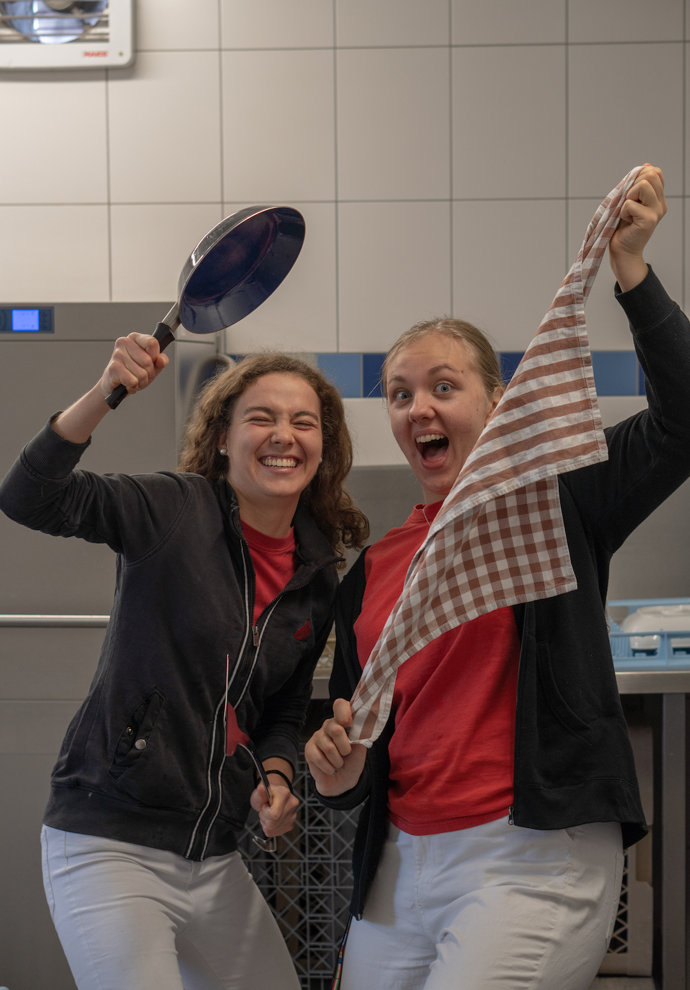 Zwei Freiwillige haben Spaß bei der Arbeit in der Spülküche