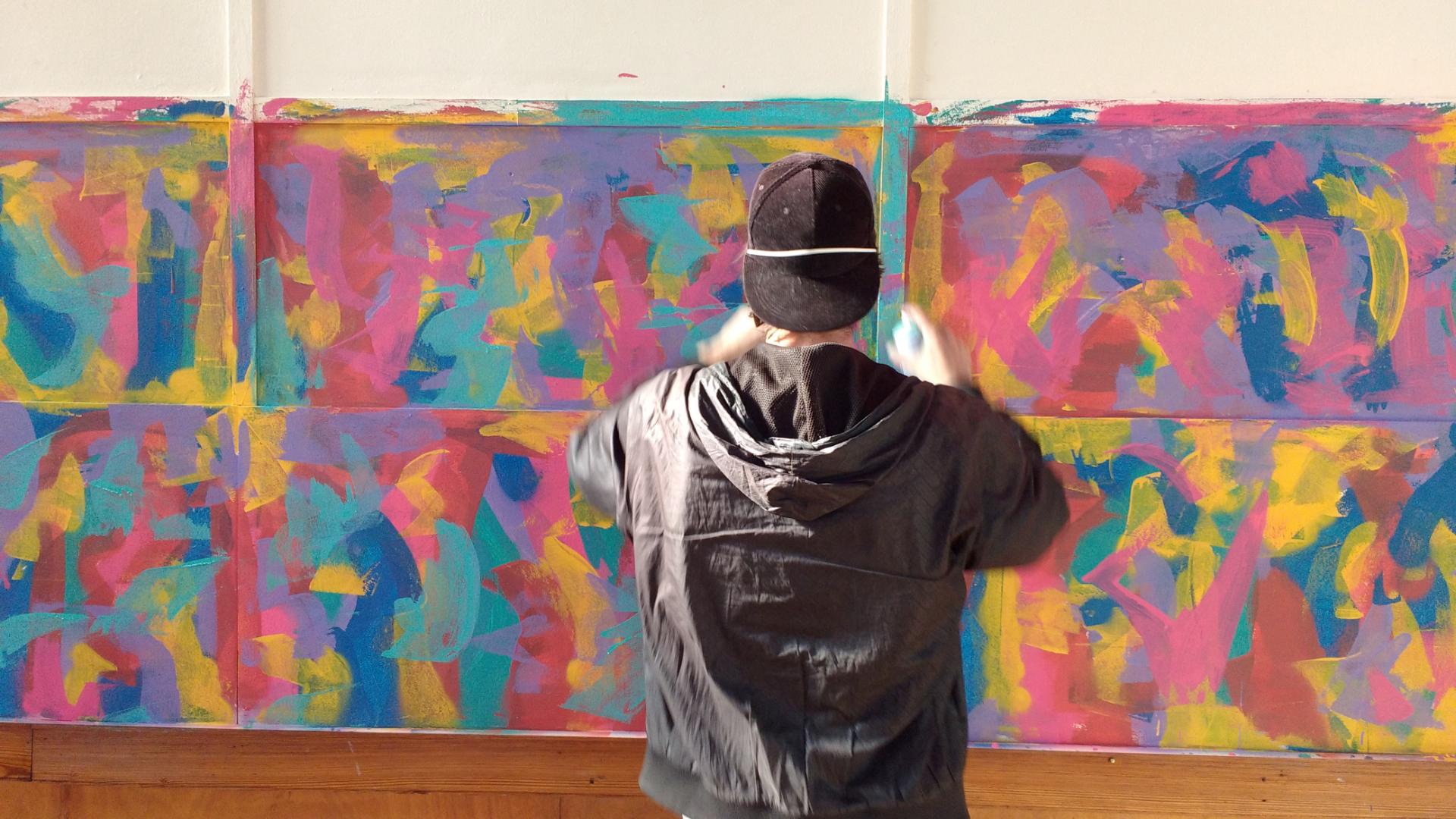 Künstler vor Grafitti-Wand