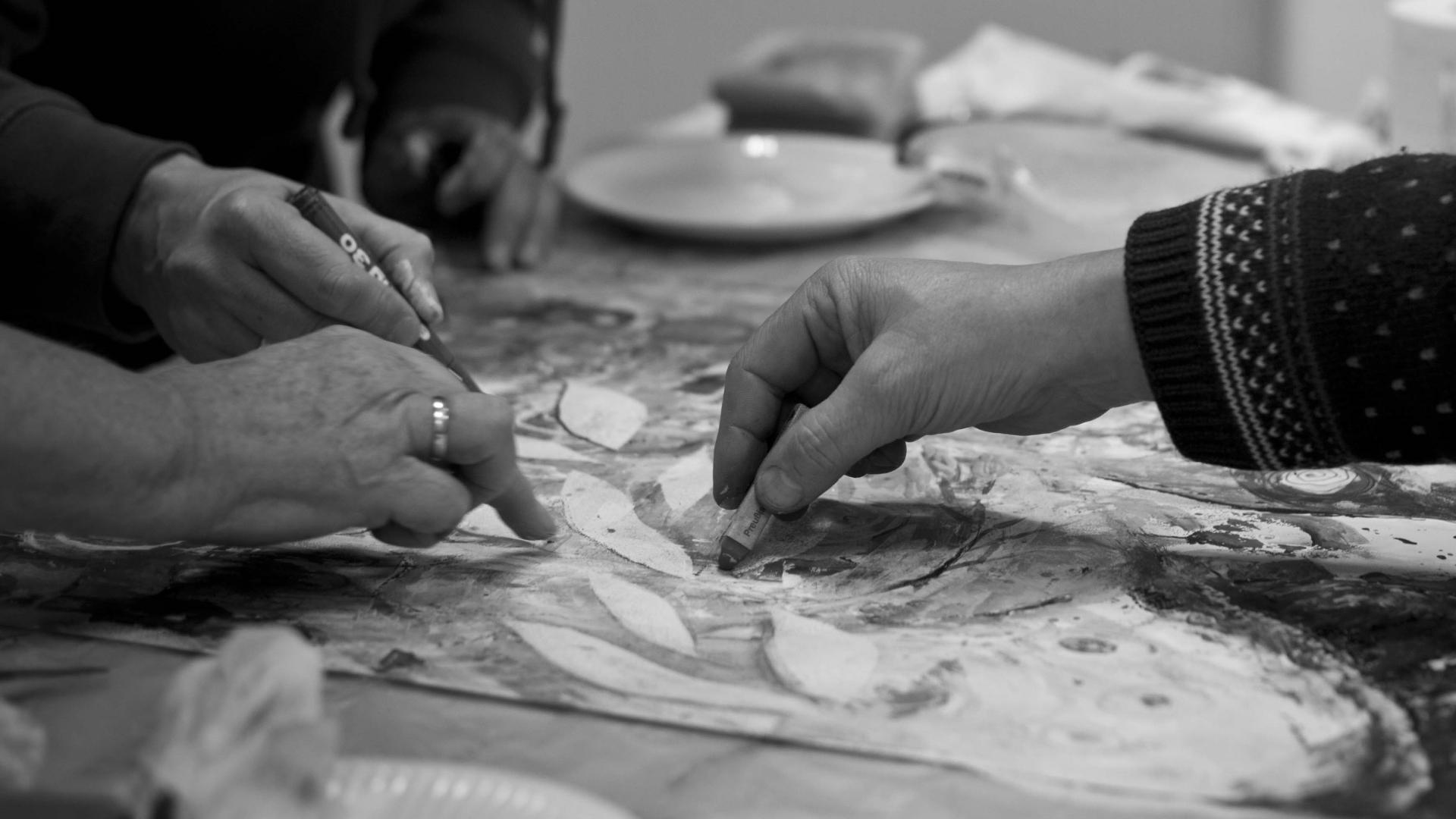 Mehrere Hände malen zusammen ein Kunstwerk (Schwarzweiß)