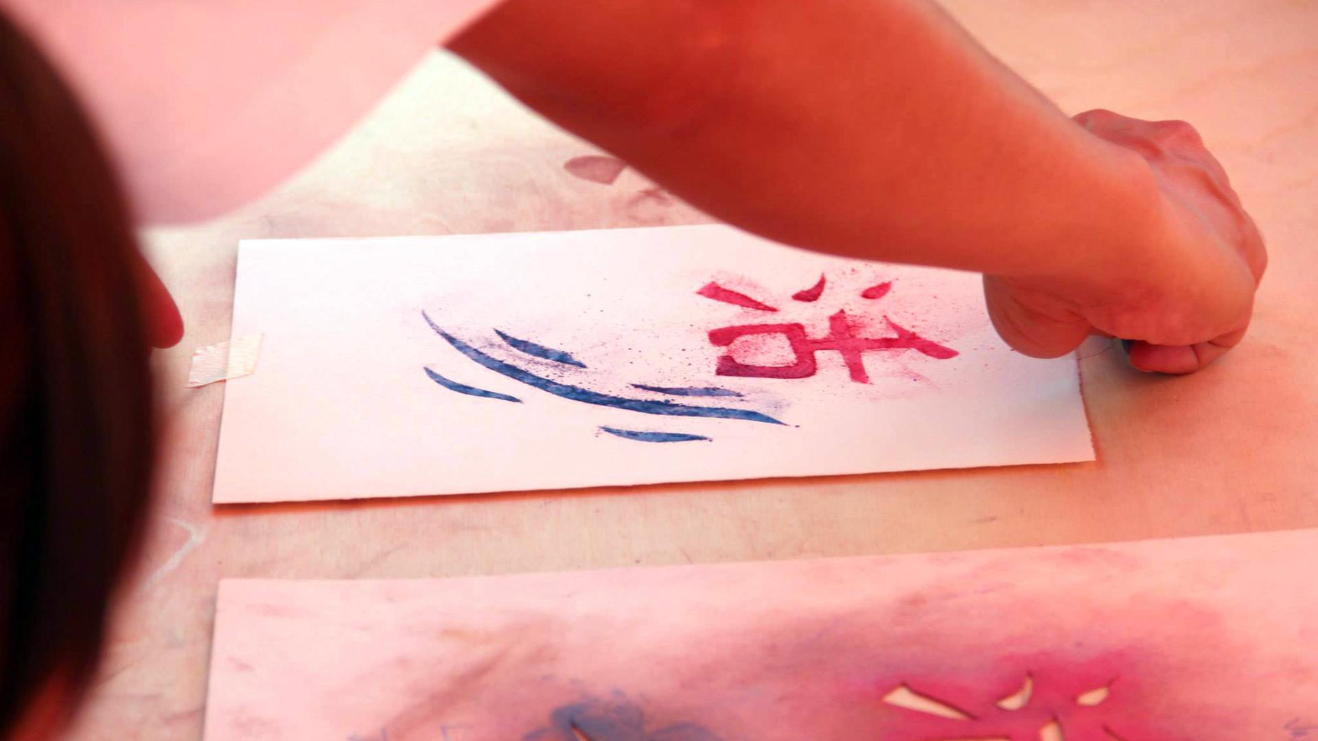 Detailaufnahme von Händen, die asiatische Schriftzeichen malen