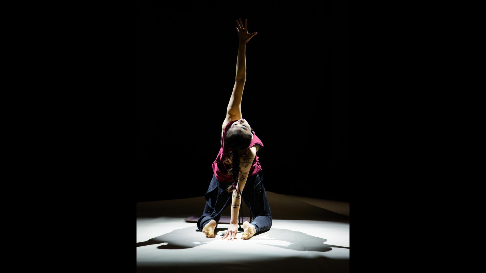 Tänzerin von hinten, die kniet und einen Arm hochstreckt