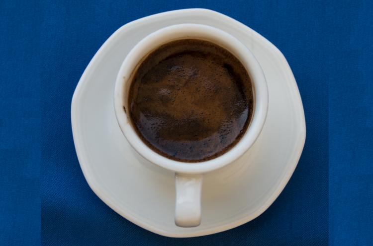 Eine Tasse mit arabischem Kaffee. Die Tasse ist aus weißem Prozellan auf blauem Hintergrund.