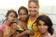 OM-Mitarbeiterin lacht mit drei Roma-Mädchen in die Kamera