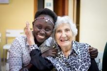 Eine junge Mitarbeiterin umarmt eine ältere Frau und beide lachen in die Kamera