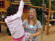 Eine Mitarbeiterin spielt mit einem Kind auf einem Klettergerät auf einem Spielplatz