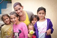 Eine OM-Mitarbeiterin lächelt mit Kindern in die Kamera