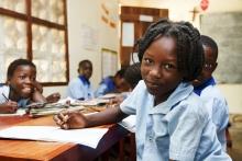 Bild aus der Schule, das vorderste Mädchen lächelt in die Kamera