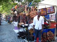 Mann steht in Südafrika vor einem Stand, an dem er Sachen verkauft