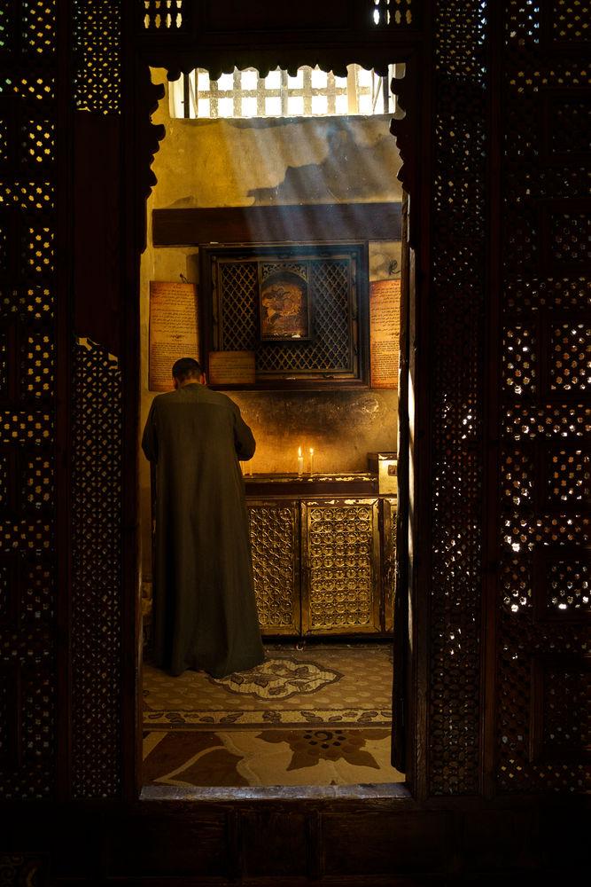 Mies sytyttää rukouskynttilän kirkossa Pohjois-Afrikassa
