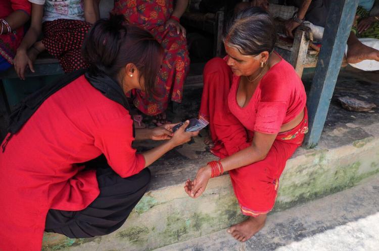 Nainen antaa toiselle naiselle ääniraamatun Etelä-Aasiassa.