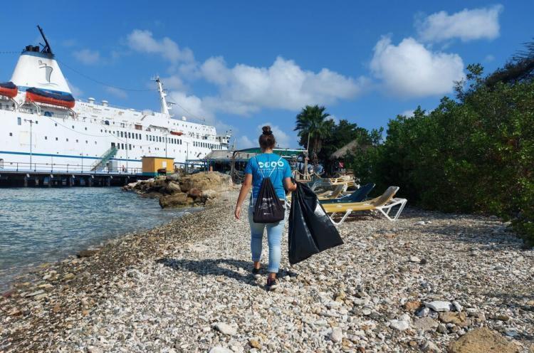 Lähetyslaiva Logos Hopen vapaaehtoinen siivoaa roskia rannalta.