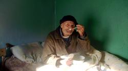 Elderly Care Moldova - old bedridden man receives food