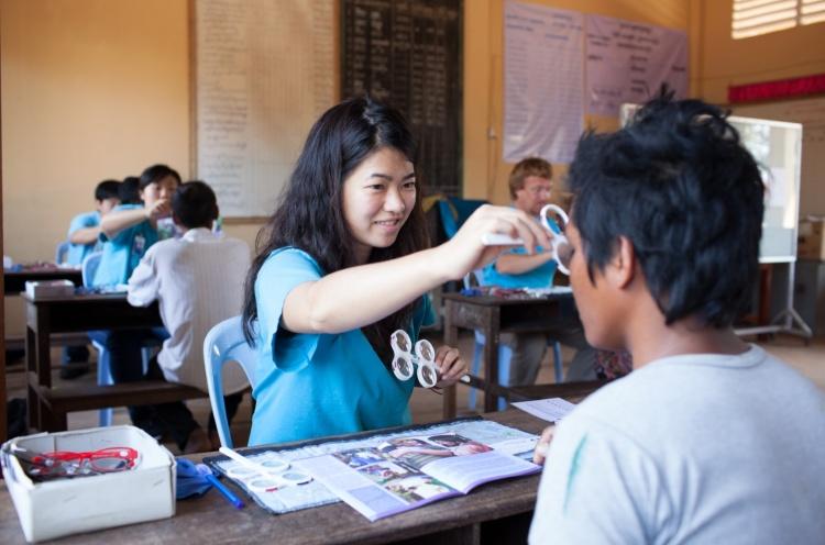 Cat Tse (UK) performs an eye exam for a local person. - Sihanoukville, Cambodia - 09. Feb 2013 - Doseong Park
