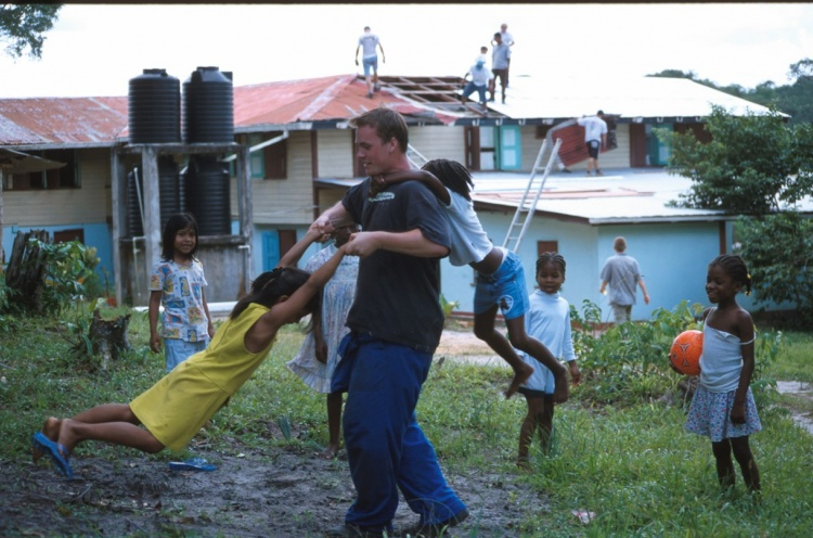 Building team putting roof on orphanage in the background, while one of the team takes time out to play with the children. - Georgetown, Guyana - 15 Aug 2002 - Susanna Burton